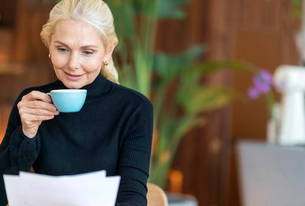 Vista frontal de uma mulher mais velha no trabalho lendo jornais enquanto toma um café