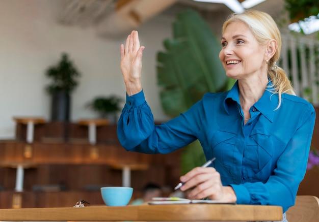 Vista frontal de uma mulher mais velha pedindo algo enquanto trabalha