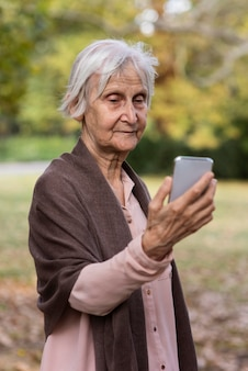 Vista frontal de uma mulher mais velha segurando um smartphone