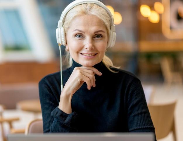 Vista frontal de uma mulher mais velha sorridente em uma teleconferência com fones de ouvido