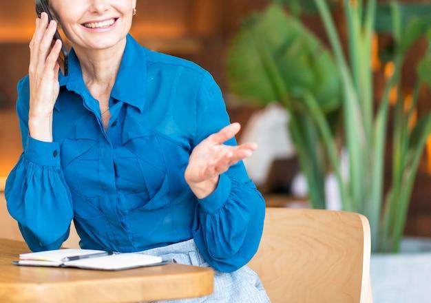 Vista frontal de uma mulher mais velha sorridente falando ao telefone enquanto trabalha