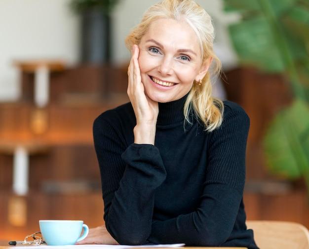 Vista frontal de uma mulher mais velha sorridente, posando enquanto toma um café
