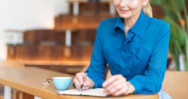 Vista frontal de uma mulher mais velha trabalhando enquanto toma um café