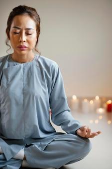 Vista frontal de uma mulher meditando ao lado de velas com espaço de cópia