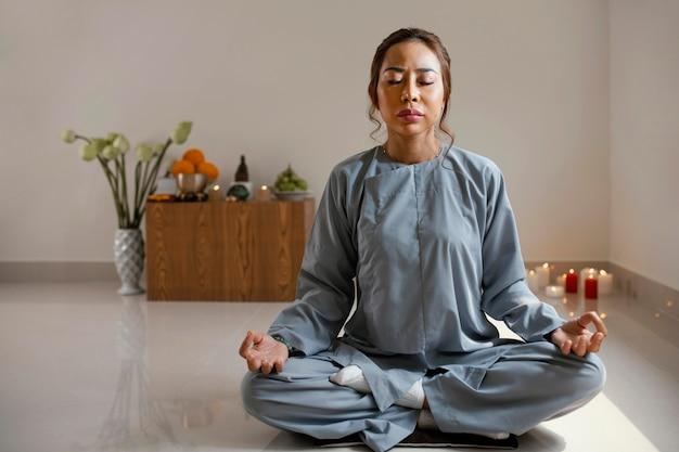 Vista frontal de uma mulher meditando em uma sala com espaço de cópia