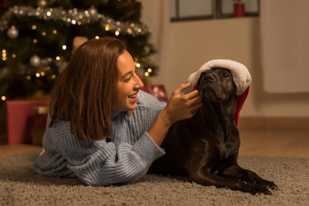 Vista frontal de uma mulher no natal com seu cachorro usando chapéu de papai noel