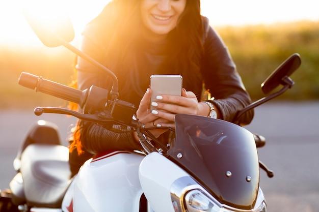 Vista frontal de uma mulher olhando para o smartphone enquanto está sentada em sua motocicleta