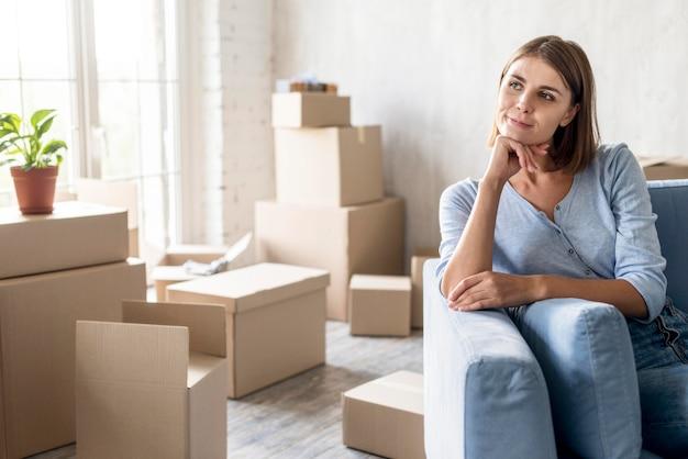 Vista frontal de uma mulher pensativa no sofá, pronta para se mudar