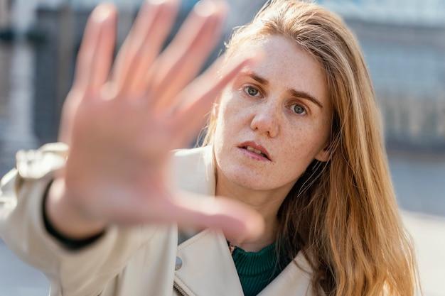 Vista frontal de uma mulher posando ao ar livre na cidade e alcançando a mão dela