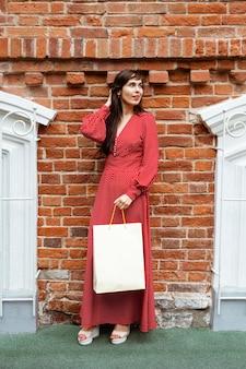 Vista frontal de uma mulher posando do lado de fora com sacolas de compras