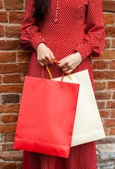 Vista frontal de uma mulher posando do lado de fora enquanto segura várias sacolas de compras
