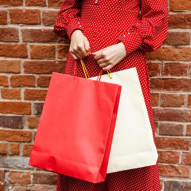 Vista frontal de uma mulher posando do lado de fora, segurando sacolas de compras