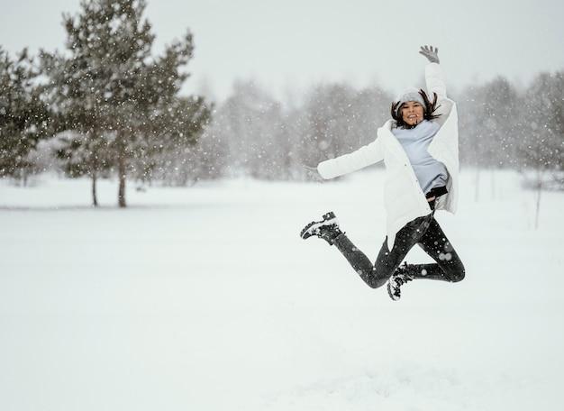 Vista frontal de uma mulher pulando no ar ao ar livre no inverno