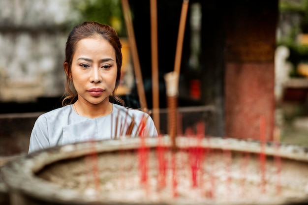 Vista frontal de uma mulher queimando incenso no templo