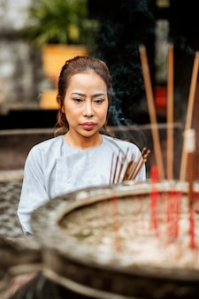 Vista frontal de uma mulher religiosa queimando incenso no templo