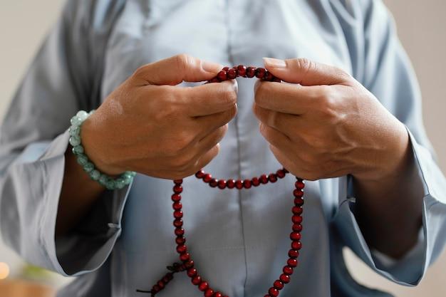Vista frontal de uma mulher segurando contas e meditando