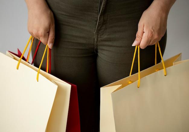 Vista frontal de uma mulher segurando muitas sacolas de compras com as duas mãos