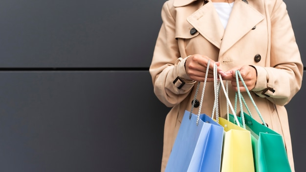 Vista frontal de uma mulher segurando sacolas de compras com espaço de cópia