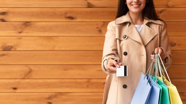 Vista frontal de uma mulher segurando sacolas de compras e oferecendo seu cartão de crédito