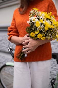 Vista frontal de uma mulher segurando um buquê de flores com uma bicicleta