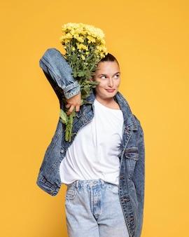 Vista frontal de uma mulher segurando um buquê de flores