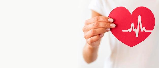 Vista frontal de uma mulher segurando um coração de papel com batimento cardíaco
