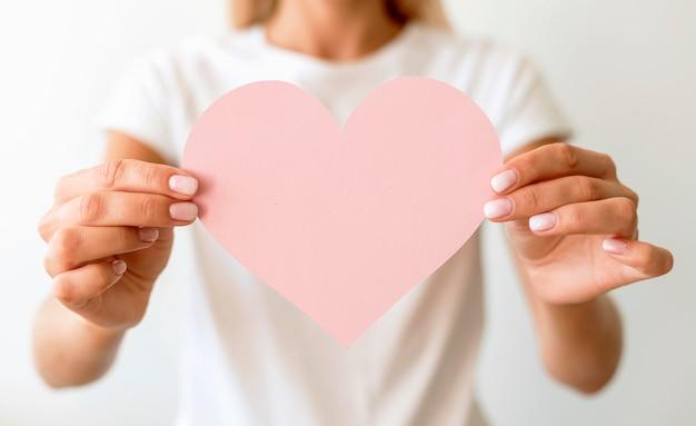 Vista frontal de uma mulher segurando um coração de papel nas mãos