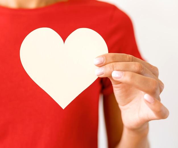 Vista frontal de uma mulher segurando um coração de papel