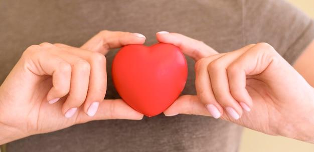 Vista frontal de uma mulher segurando um formato de coração nas mãos