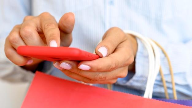 Vista frontal de uma mulher segurando um smartphone e sacolas de compras para a cibernética segunda-feira