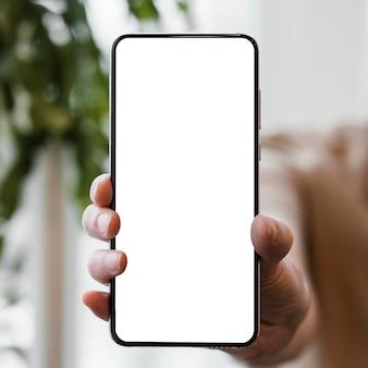 Vista frontal de uma mulher segurando um smartphone