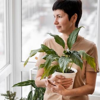Vista frontal de uma mulher segurando um vaso de planta