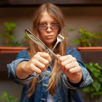 Vista frontal de uma mulher segurando uma faca e um garfo em um x