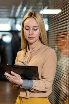 Vista frontal de uma mulher segurando uma prancheta no local de trabalho Foto gratuita