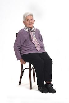Vista frontal de uma mulher sênior sentada na cadeira, olhando para a frente e sorrindo em branco