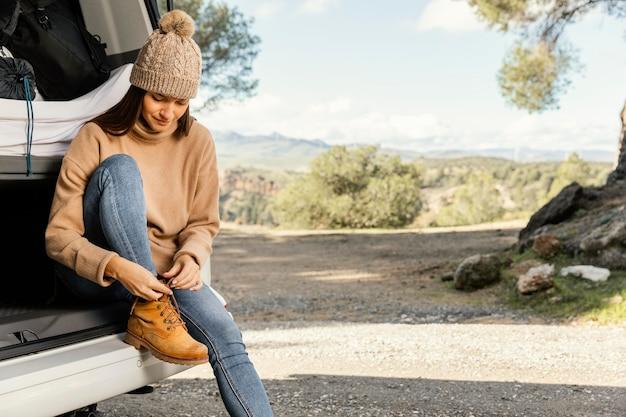 Vista frontal de uma mulher sentada no porta-malas do carro durante uma viagem e amarrando cadarços de sapato