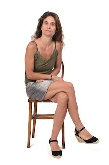 Vista frontal de uma mulher séria em saia jeans, sentada em uma cadeira e de branco, pernas cruzadas