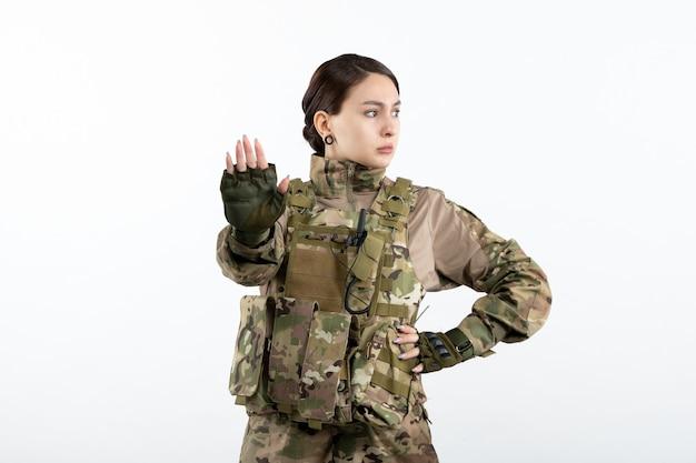 Vista frontal de uma mulher soldado camuflada pedindo para parar com uma parede branca