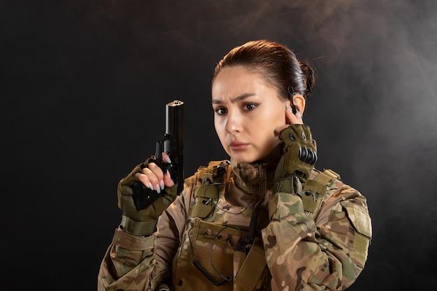 Vista frontal de uma mulher soldado com arma de uniforme na parede preta esfumaçada