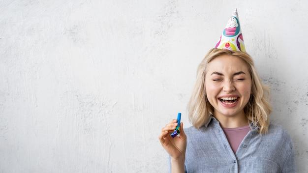 Vista frontal de uma mulher sorridente com chapéu de festa e espaço de cópia