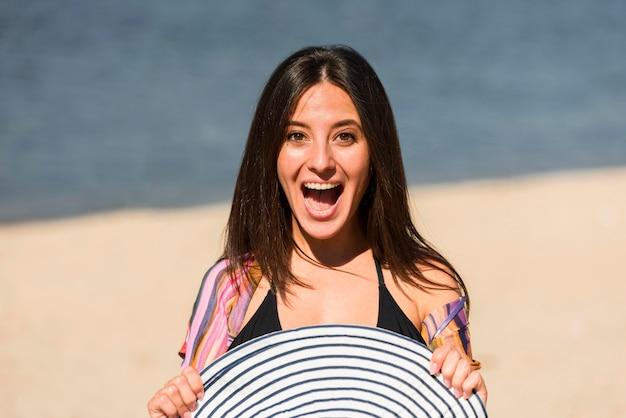 Vista frontal de uma mulher sorridente com chapéu na praia