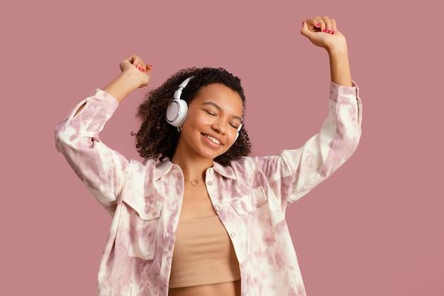 Vista frontal de uma mulher sorridente com fones de ouvido dançando
