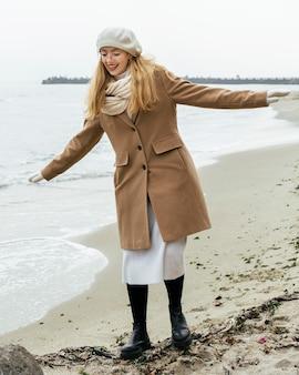 Vista frontal de uma mulher sorridente com luvas na praia durante o inverno