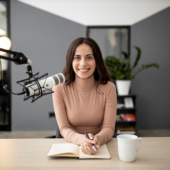 Vista frontal de uma mulher sorridente com microfone em um estúdio de rádio