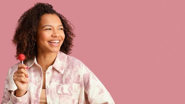 Vista frontal de uma mulher sorridente com pirulito e espaço de cópia
