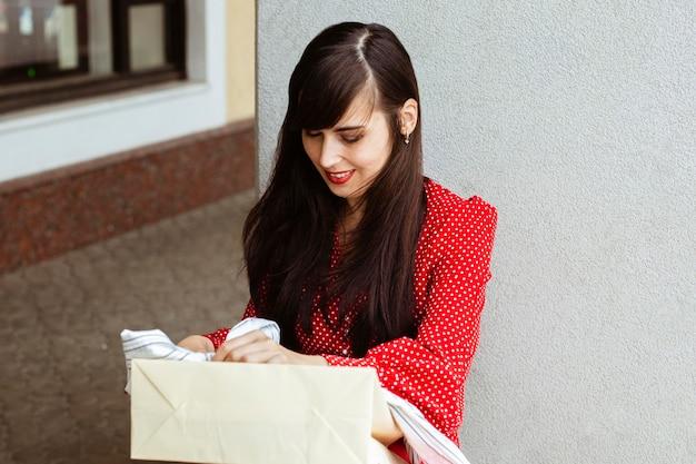 Vista frontal de uma mulher sorridente com sacola de compras e roupas à venda