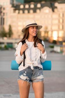 Vista frontal de uma mulher sorridente com um chapéu carregando uma mochila enquanto viaja sozinho