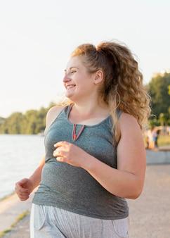 Vista frontal de uma mulher sorridente correndo à beira do lago