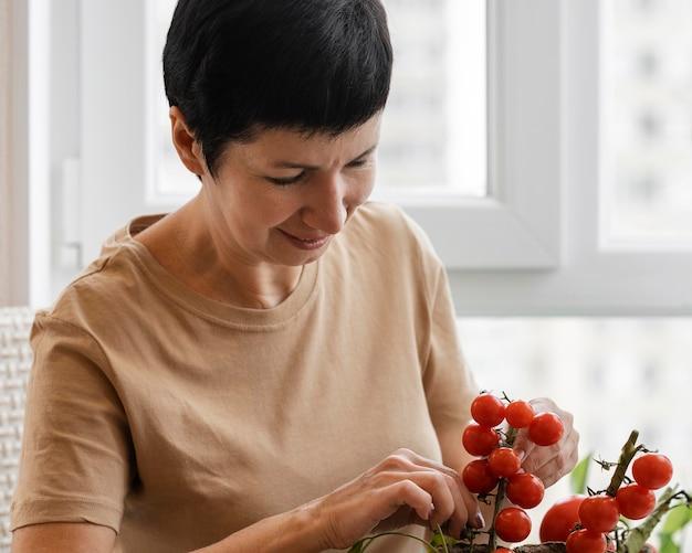 Vista frontal de uma mulher sorridente cuidando de uma planta de tomate de interior