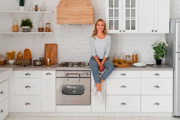 Vista frontal de uma mulher sorridente em pé na cozinha